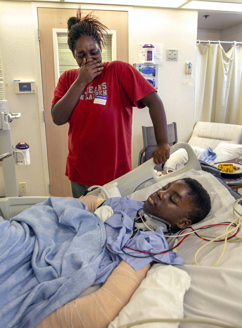 Thylicia McKnight, above, cries over her son Lennie Modica, 9, who is in recovery in the pedia ...