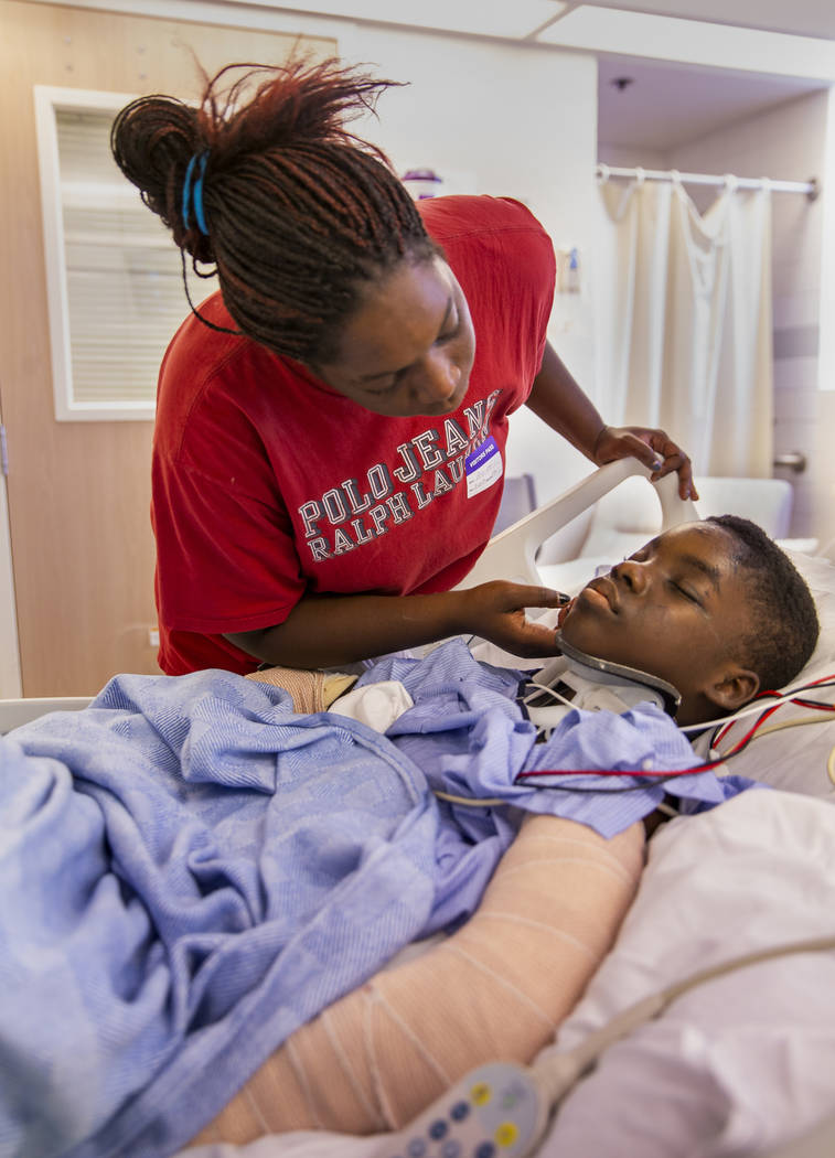 Thylicia McKnight, above, attempts to wake her son Lennie Modica, 9, who is in recovery in the ...