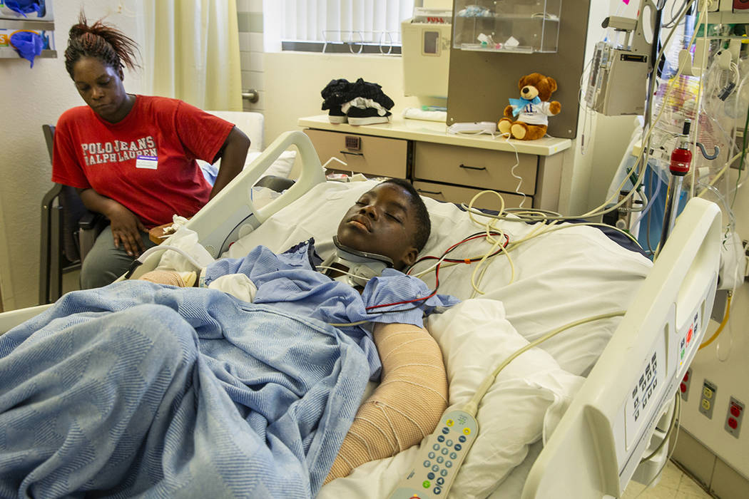 Lennie Modica, 9, right, sleeps as his mother Thylicia McKnight stays with him during recovery ...