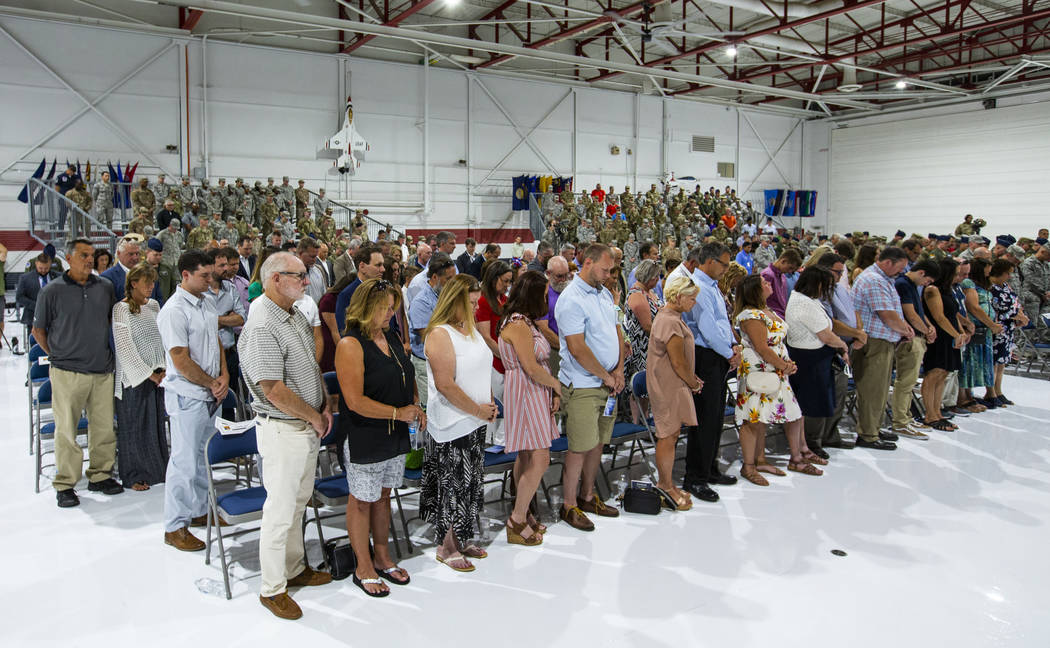 Family, friends and invited guests stand for a prayer during the Assumption of Command Ceremony ...