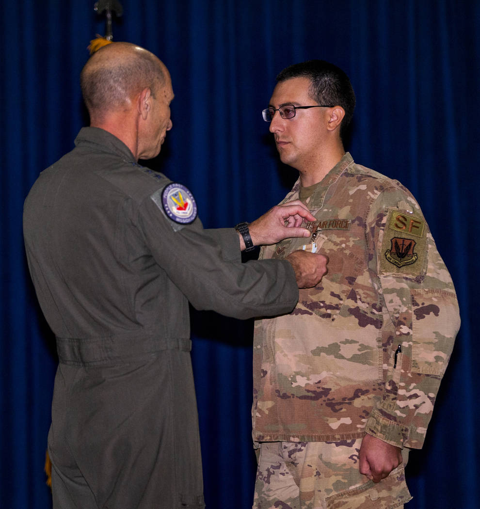 Gen. Mike Holmes, Commander of Air Combat Command, left, presents Staff Sgt. Kenneth DeLongcham ...