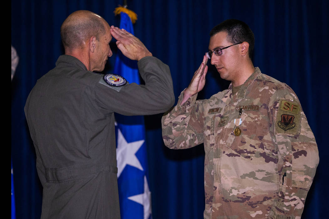 Gen. Mike Holmes, Commander of Air Combat Command, left, salutes with Staff Sgt. Kenneth DeLong ...