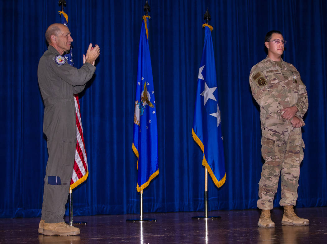 Gen. Mike Holmes, Commander of Air Combat Command, left, claps for Staff Sgt. Kenneth DeLongcha ...