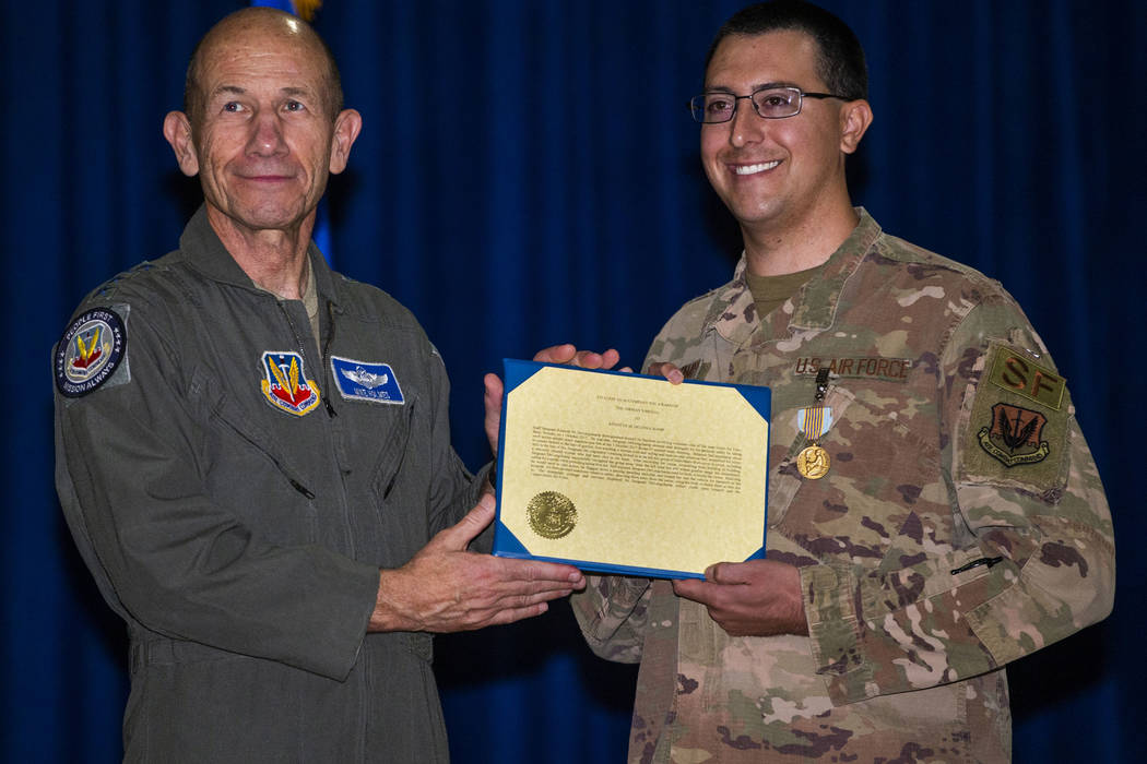 Gen. Mike Holmes, Commander of Air Combat Command, left, poses for a photo with Staff Sgt. Kenn ...