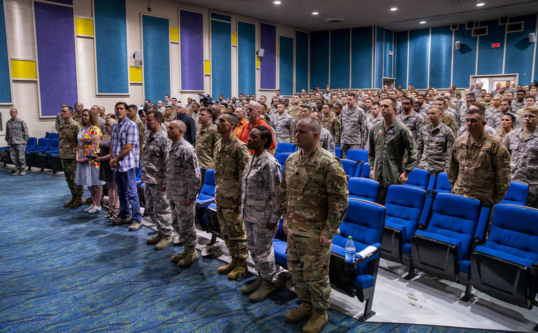 Family, friends and invited guests stand on behalf of Staff Sgt. Kenneth DeLongchamp during the ...