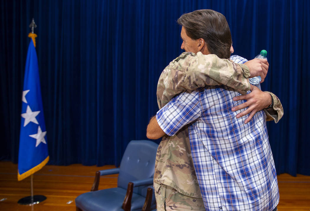 Staff Sgt. Kenneth DeLongchamp, left, hugs his father Ken at Nellis Air Force Base on Friday, J ...
