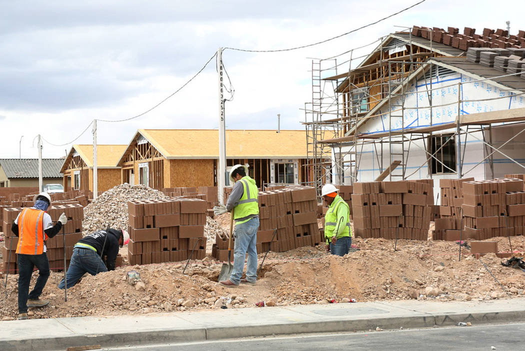 Construction workers build wall during the new construction of LGI Homes at the Intersection of ...