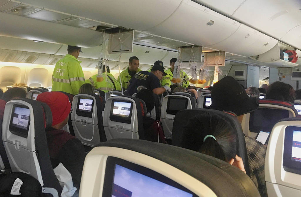 Emergency workers treat a passenger on an Air Canada flight to Australia that was diverted and ...