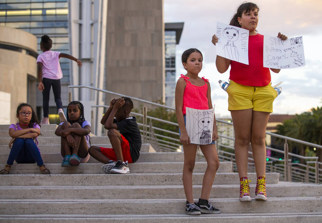 Diana Tarin, 8, left, and her sister Cecilia, 11, stand with handmade signs during Lights for L ...