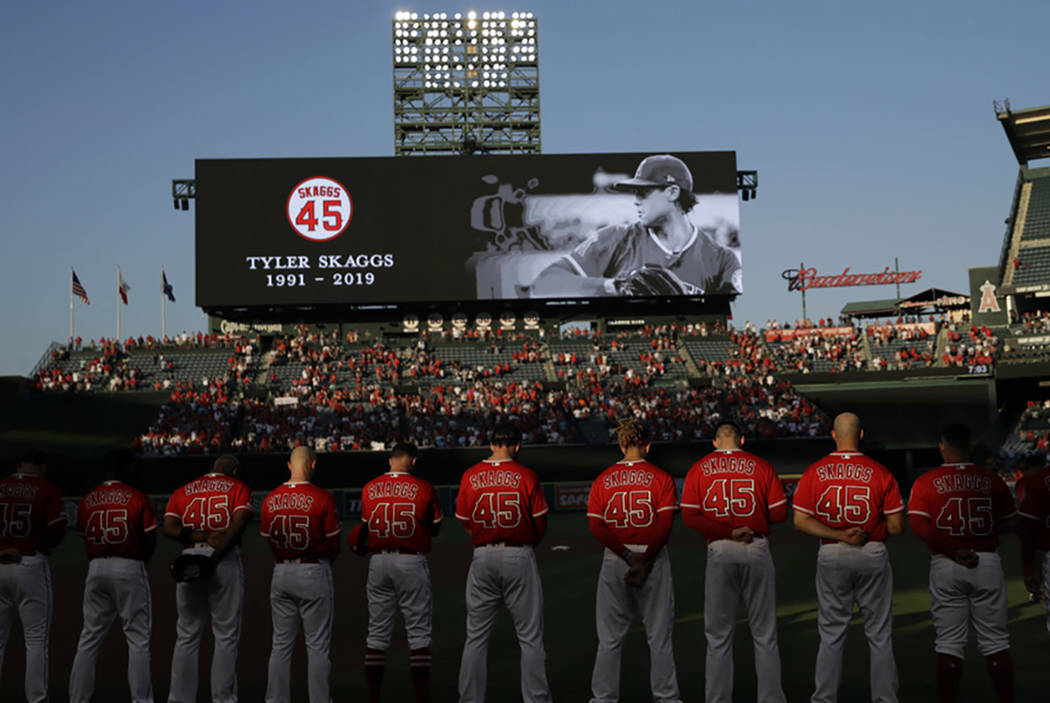 Members of the Los Angeles Angels observe a moment of silence for teammate Tyler Skaggs, before ...