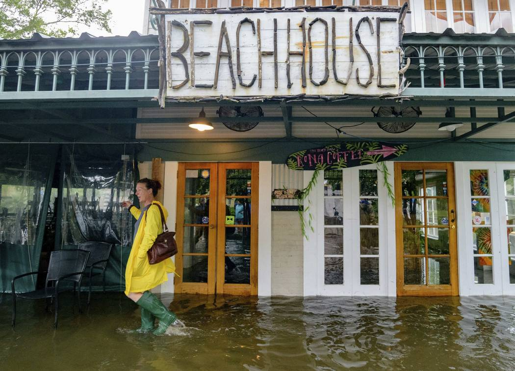 Aimee Cutter, the owner of Beach House restaurant, walks through water surge from Lake Pontcha ...