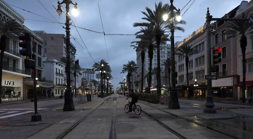 A man rides a bicycle on Canal Street Saturday, July 13, 2019, in New Orleans, as Tropical Stor ...