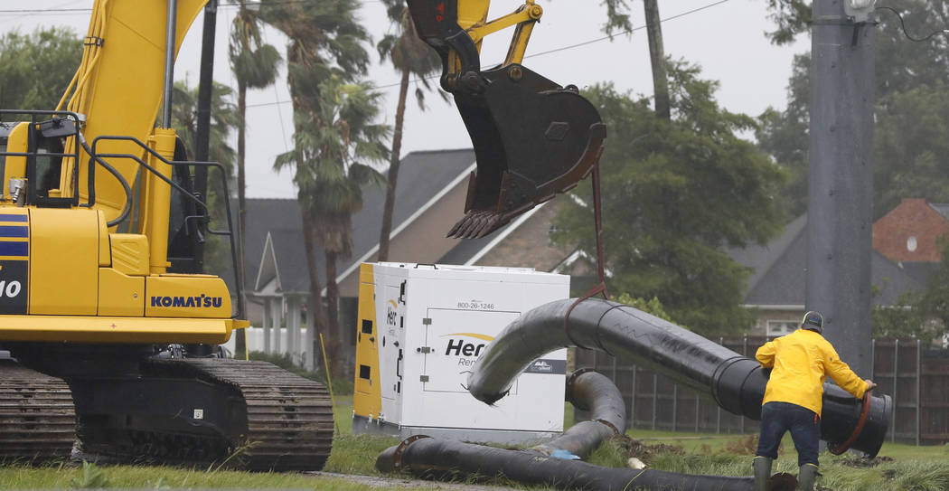 A worker maneuvers a section of pipe to the ground as a crew raced to install drainage pumps in ...