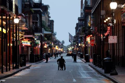A man in a wheelchair makes his way down Bourbon Street in the French Quarter Saturday, July 13 ...