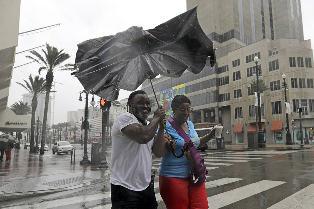 Karon Hill, left, and Celeste Cruz battle the wind and rain from Hurricane Barry as it nears la ...