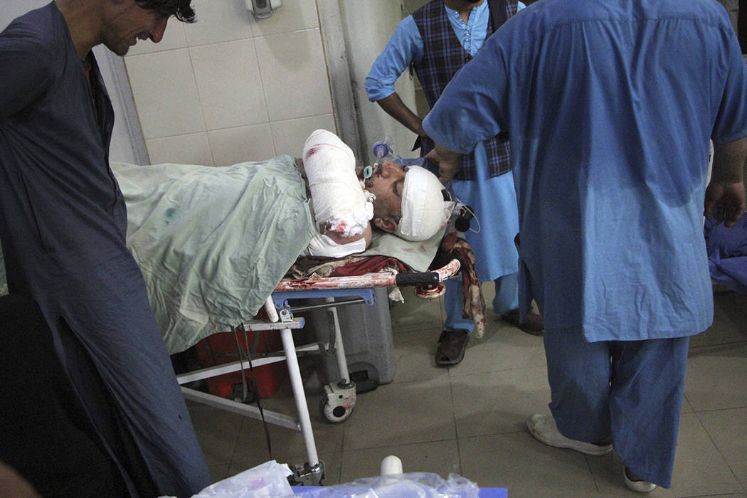 A wounded man receives treatment in a hospital after a suicide attack on the outskirts of Nanga ...