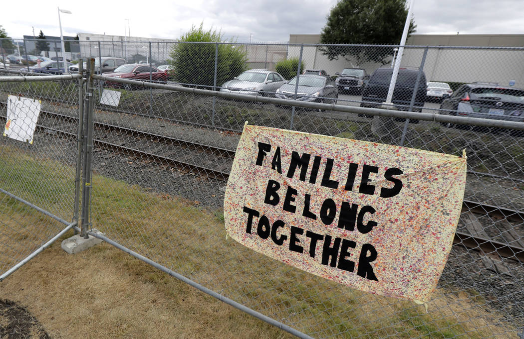 """FILE - This July 10, 2018 file photo shows a sign that reads """"Families Belong Together"""" on a fe ..."""