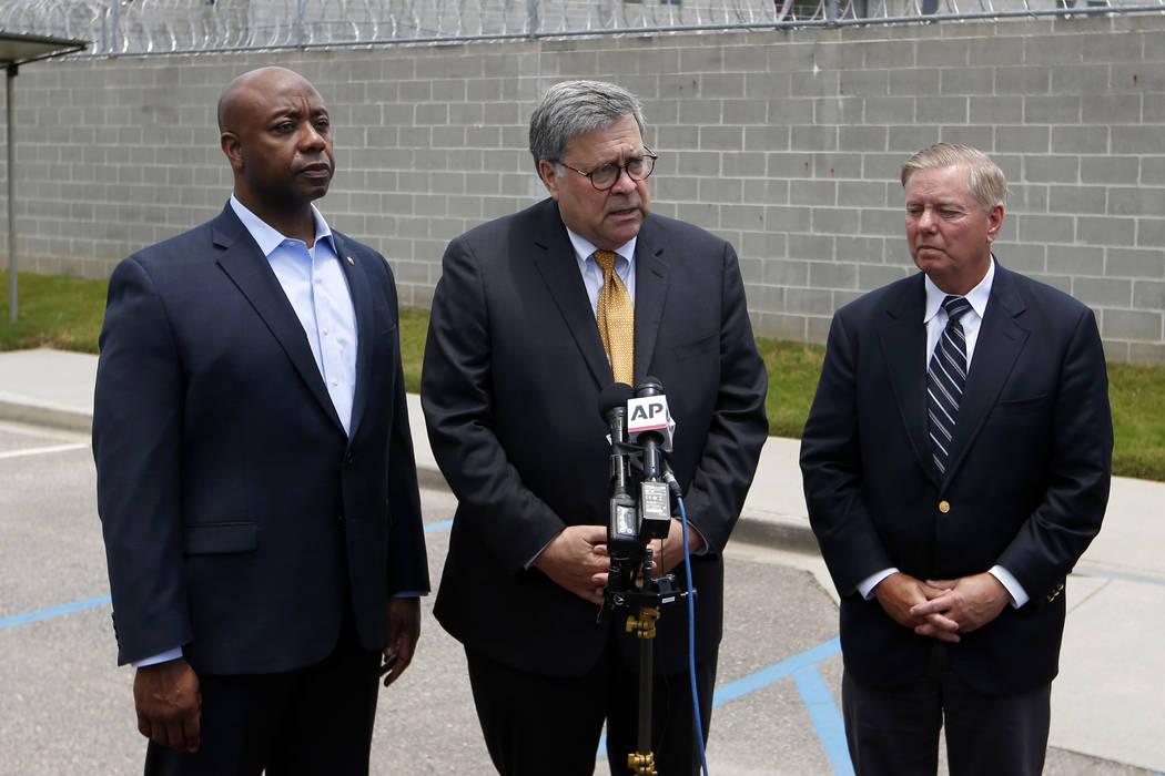 Attorney General William Barr, center, stands with Sen. Tim Scott, R-S.C., left, and Sen. Linds ...