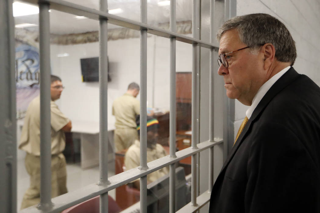 Attorney General William Barr watches as inmates work in a computer class during a tour of a fe ...