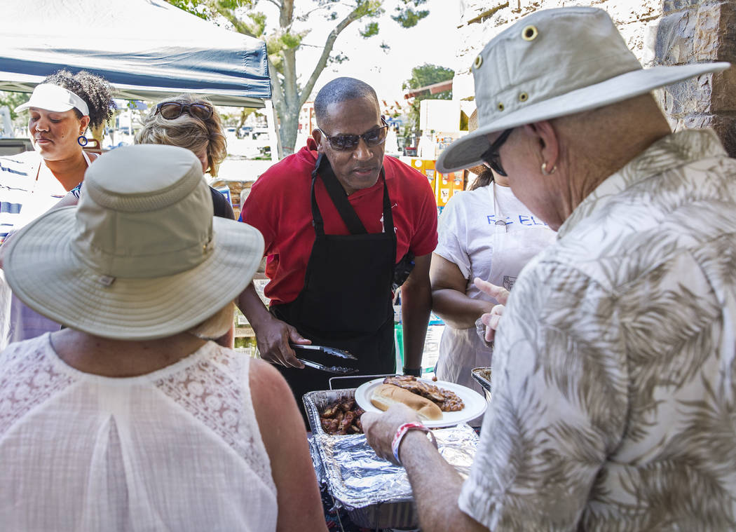 Clark County Commissioner Lawrence Weekly, middle, serves food to guests during the 5th Annual ...