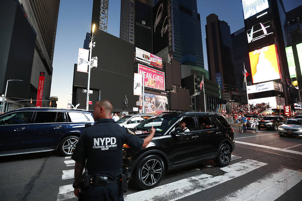 A police officer directs traffic in Times Square during a widespread power outage, Saturday, Ju ...