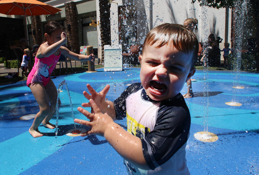 Children, including Caleb Lugrand, 2, right, of Las Vegas play at a splash pad on a hot day at ...