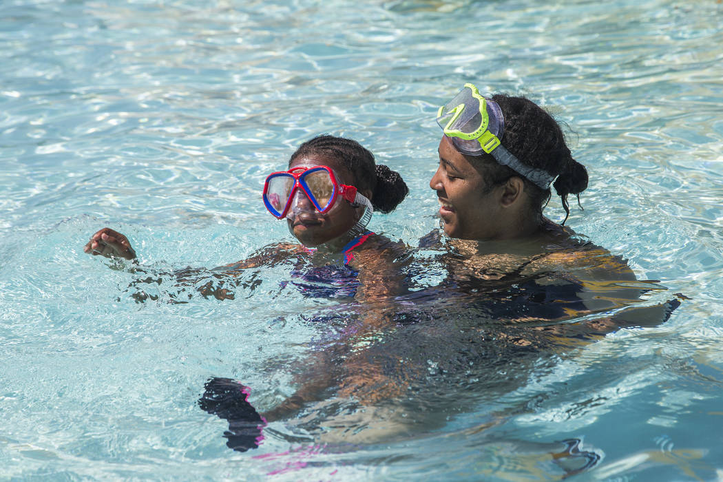 Tamia Boston, 17, holds her cousin Makaylia McNeill, 9, in a pool at Cowabunga Bay water park i ...