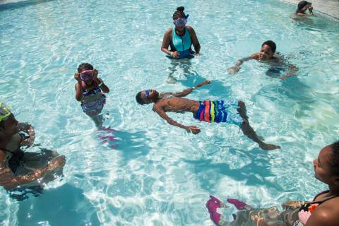 Dillon Hanger, 12, floats in a pool surrounded by his family Tamia Boston, 17, from left, Makay ...