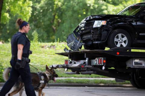 An automobile believed to be driven by a suspect is removed from the scene during an active inv ...
