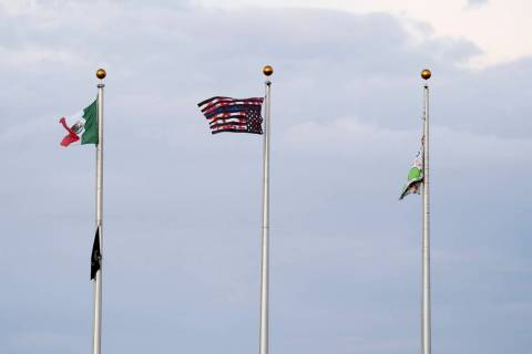 This Friday, July 12, 2019, photo shows a Mexican flag, from left, an upside down U.S. flag wit ...
