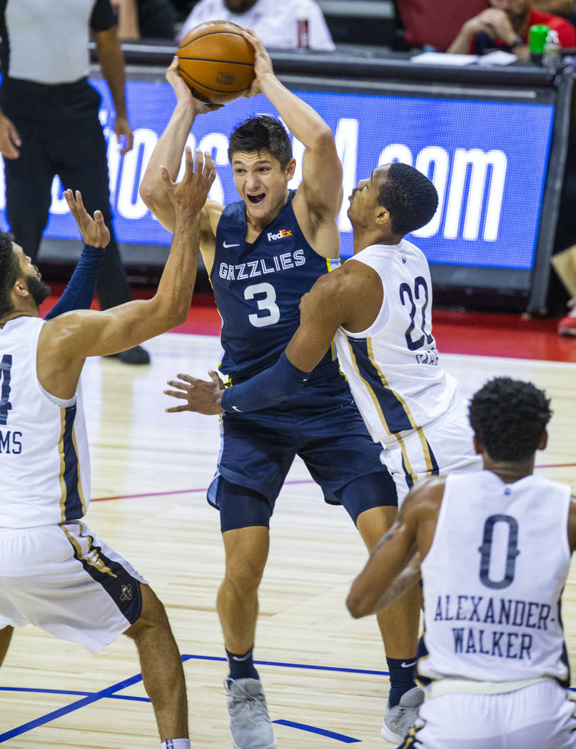 Memphis Grizzlies guard Grayson Allen, center, looks to pass over New Orleans Pelicans guard To ...