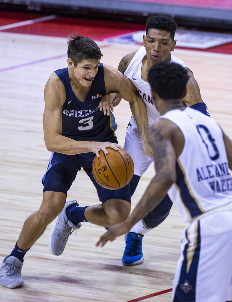Memphis Grizzlies guard Grayson Allen, left, drives the lane under tight defense by New Orleans ...