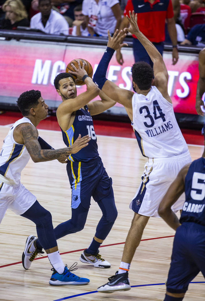 Memphis Grizzlies guard Tyler Harvey, center, looks to pass from between New Orleans Pelicans f ...