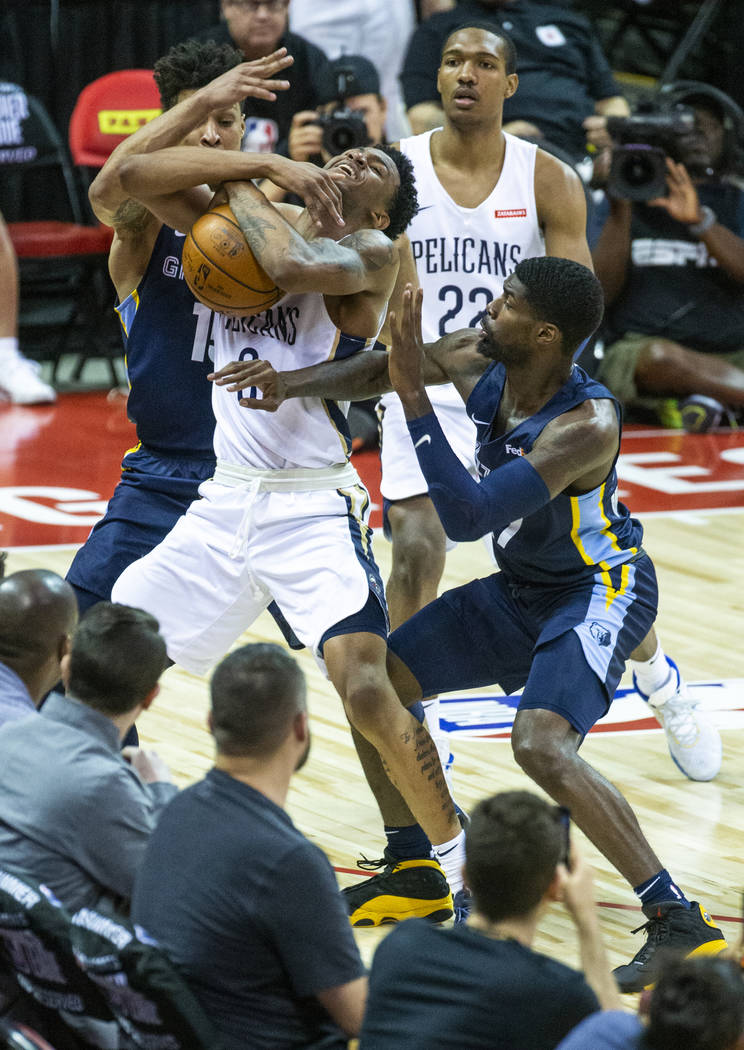 New Orleans Pelicans guard Nickeil Alexander-Walker, center, fights to keep the ball from Memph ...