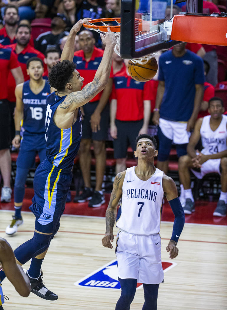 Memphis Grizzlies forward Brandon Clarke, left, dunks the ball late as New Orleans Pelicans for ...