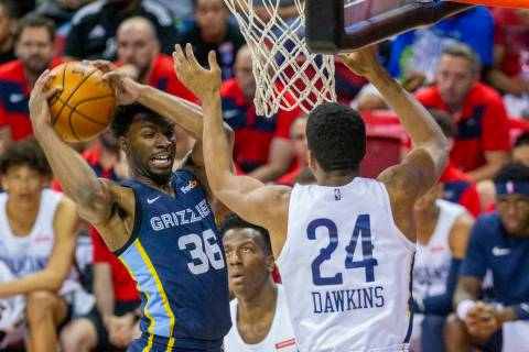 Memphis Grizzlies guard Keenan Evans, left, pills down a rebound over New Orleans Pelicans guar ...