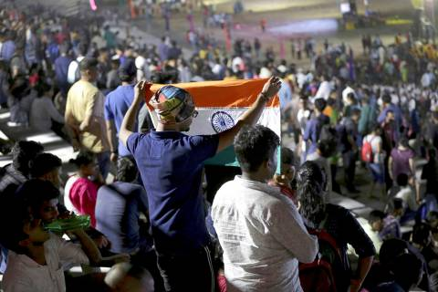 An Indian spectator folds a flag as others leave after the Chandrayaan-2 mission was aborted at ...