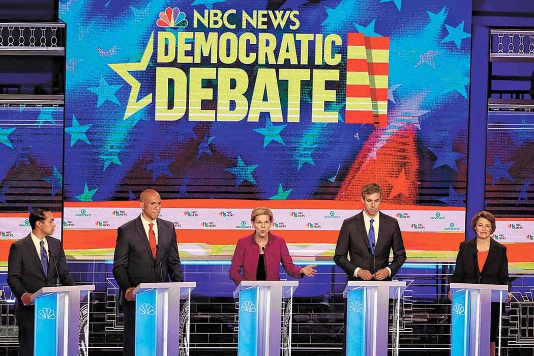 Democratic presidential candidate Sen. Elizabeth Warren, D-Mass., center, answers a question, d ...