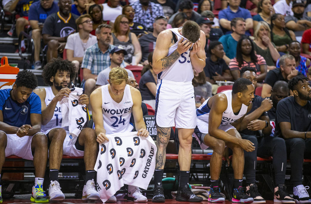 Minnesota Timberwolves forward Mitchell Creek wipes his eyes while standing beside his teammate ...