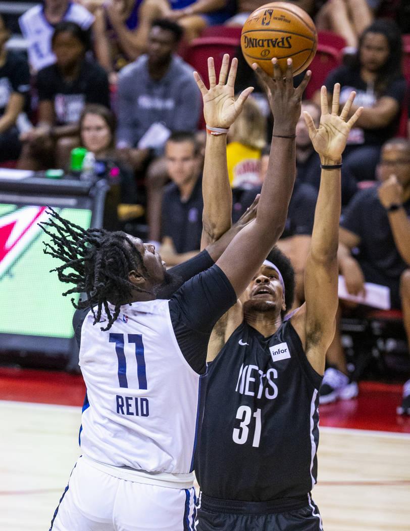 Minnesota Timberwolves center Naz Reid, left, gets off a shot over the Brooklyn Nets center Jar ...
