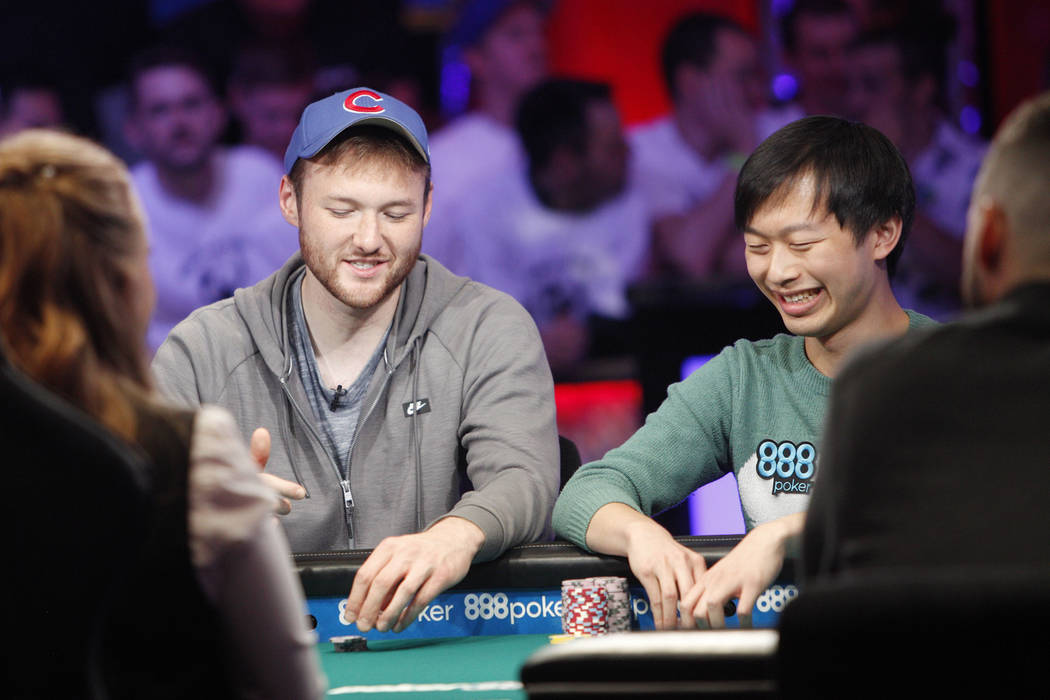 Kevin Maahs, left, talks with Timothy Su at the main event final table during the World Series ...