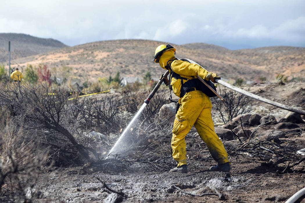 A firefighter hoses down an area in Reno in October 2016. (Mike Higdon/The Reno Gazette-Journal ...