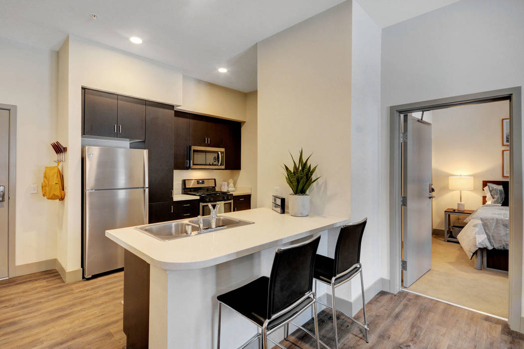 Each apartment includes a living room, television and entertainment-style kitchen with stainles ...