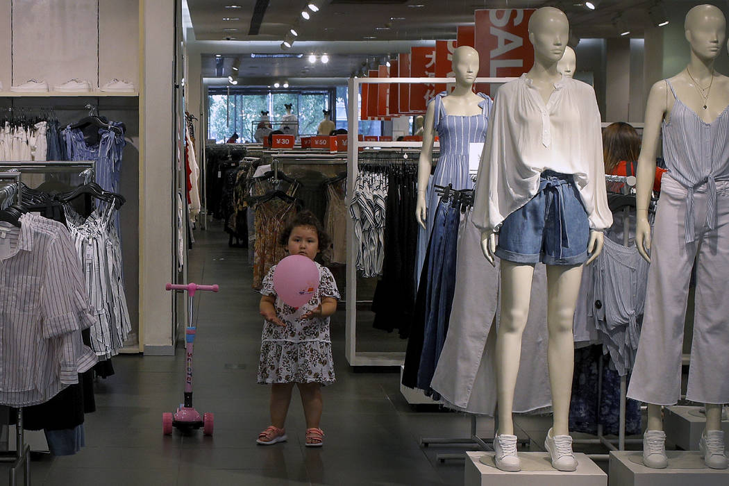 A child plays with a balloon at a clothing store having a promotion sale in Beijing, Monday, Ju ...
