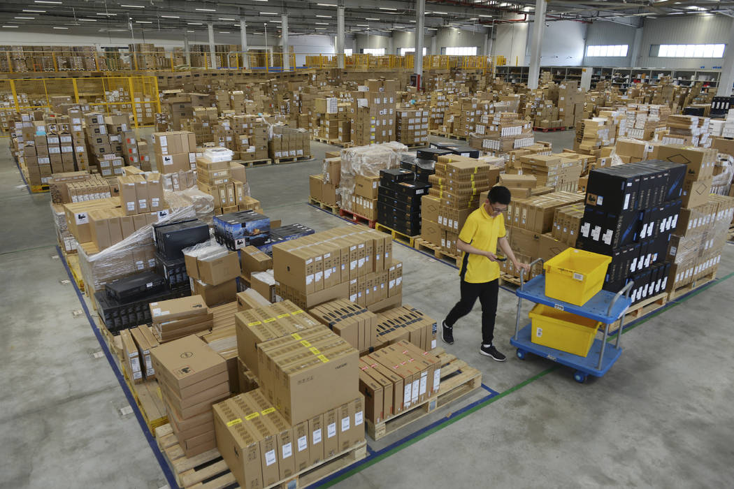 In this Saturday, June 15, 2019, photo, a worker passes by goods piled up at a warehouse in Nan ...