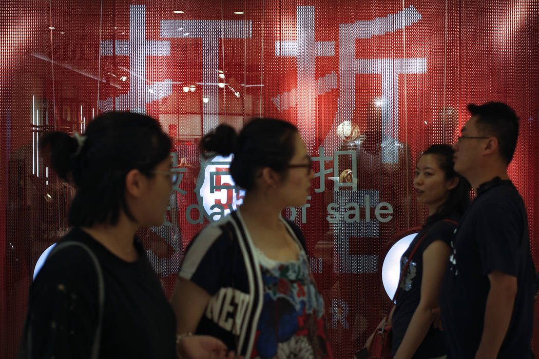 People walk by a fashion retailer having promotion sale at a shopping mall in Beijing, Monday, ...