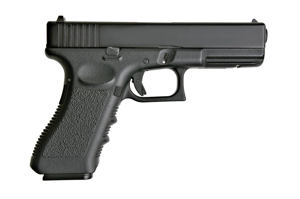 side view of handgun on pure white background