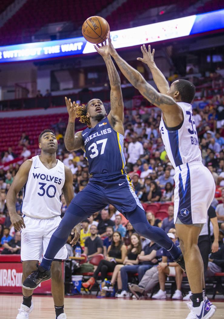 Memphis Grizzlies guard Paris Lee, left, gets off a shot over the Minnesota Timberwolves guard ...