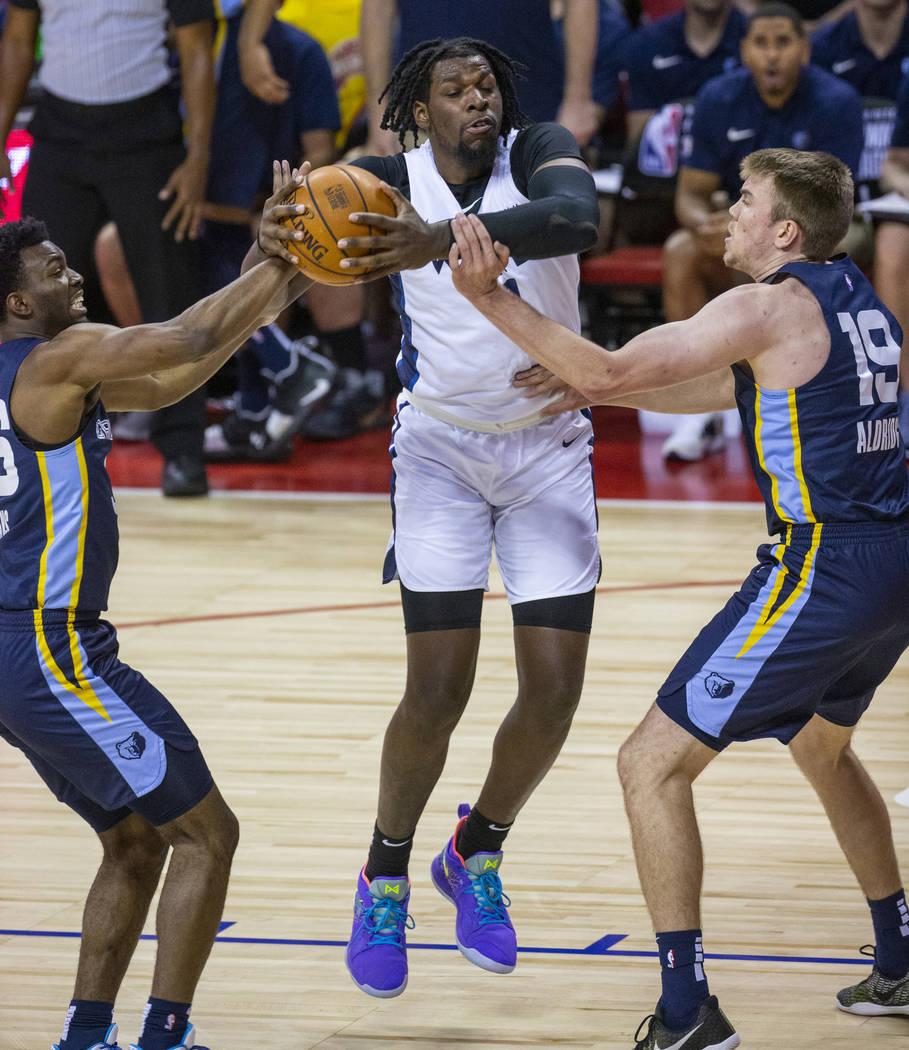 Minnesota Timberwolves center Naz Reid, center, fights for a rebound with Memphis Grizzlies gua ...