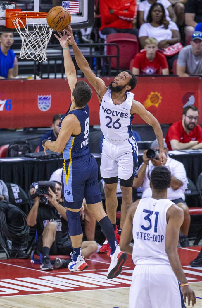 Memphis Grizzlies guard Dusty Hannahs, left, has a shot rejected by Minnesota Timberwolves guar ...
